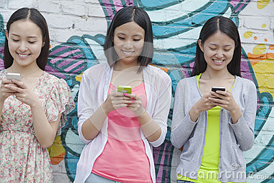 Three smiling young woman standing side by side and texting on their phones in front of a wall with graffiti