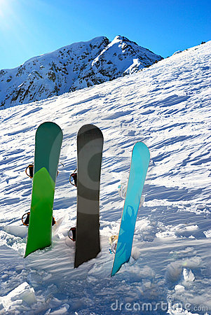 Three snowboards under sun