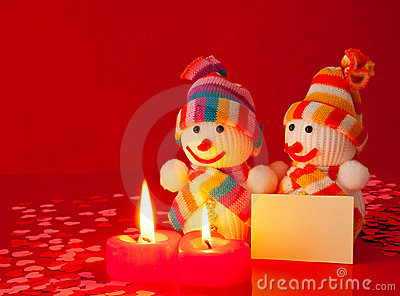 Three snowmen with two burning candles
