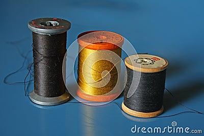 Three spools of thread on blue background