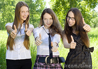 Three student girl with thumbs-up in the park