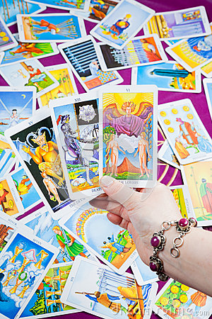 Three tarot cards held in hand.