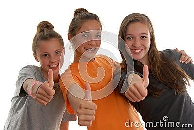 Three teenage girls all thumbs up smiling studio