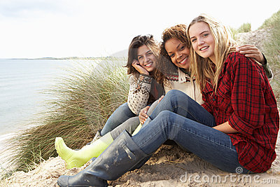 Three Teenage Girls Sitting In Sand Dunes