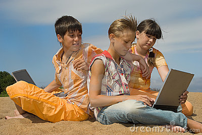 Three teens  with laptops