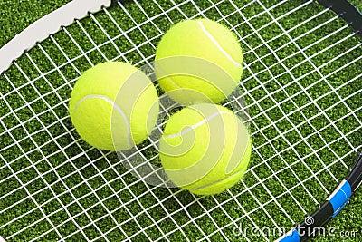 Three tennis balls lie on a tennis racket strings. over green la