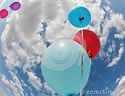 Three vivid color balloons in blue sky