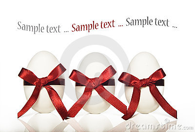 Three white candy easter eggs with red ribbons