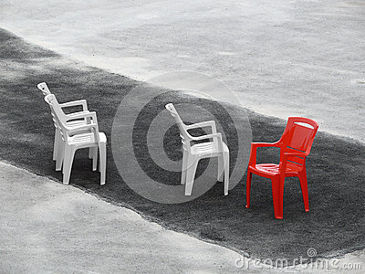 Three white chairs and one red on dark asphalt