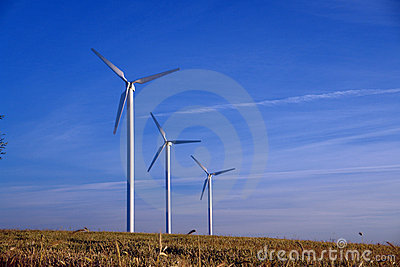 Three wind turbines in a row, rural landscape.