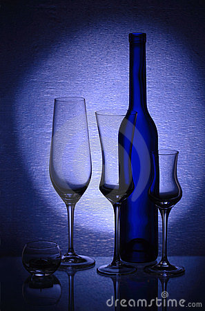 Three wineglasses, a candlestick and a bottle