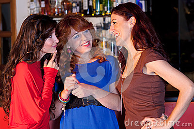 Three women in a bar talking.