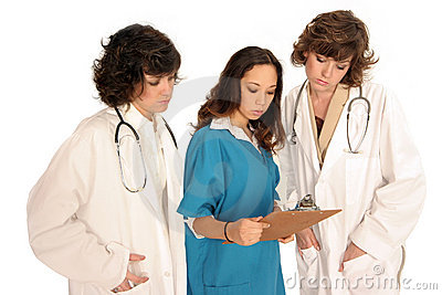 Three women medical professionals looking over report