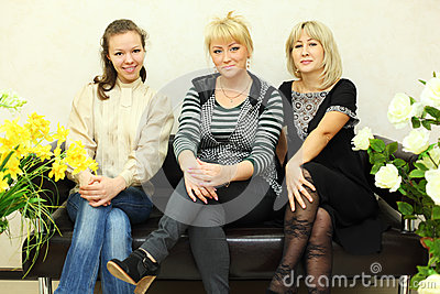 Three women sit on black leather couch