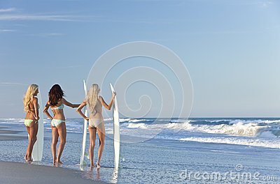 Three Women Surfers With Surfboards At Beach