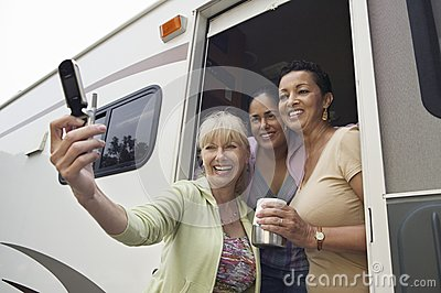 Three women using camera phone in motor home