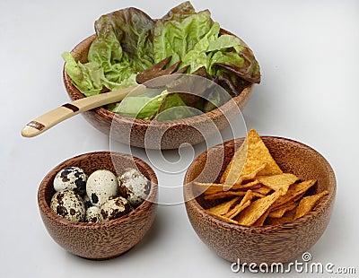 Three wooden bowls with fresh green salad, quail e