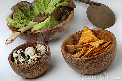 Three wooden bowls with fresh green salad, quail e