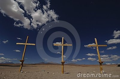 Three wooden crosses in desert with blue sky