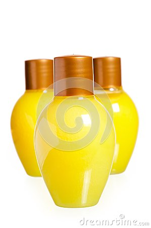 Three yellow bottles of cosmetics