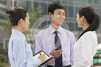 Three young business people talking and smiling outdoors, Beijing