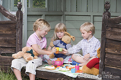 Three young children in shed playing tea