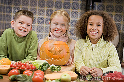 Three young friends on Halloween with pumpkin