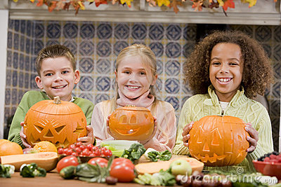 Three young friends on Halloween with pumpkins