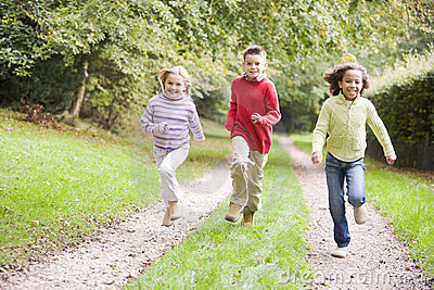 Three young friends running on a path outdoors