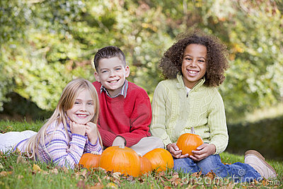 Three young friends sitting on grass with pumpkins