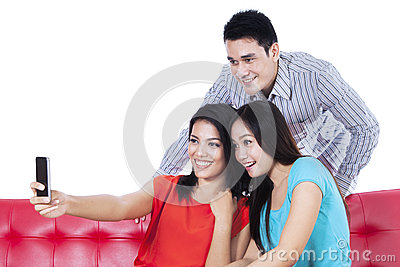Three young friends taking photo by mobile phone