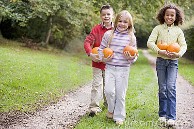 Three young friends walking on path with pumpkins