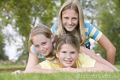 Three young girl friends piled on each other