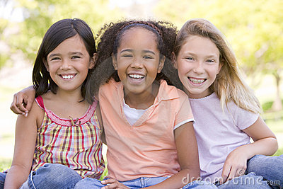 Three young girl friends sitting outdoors