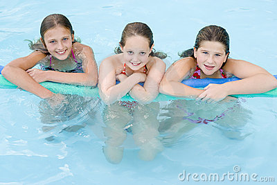 Three young girl friends in swimming pool