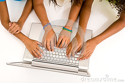 Three young girls typing on a laptop