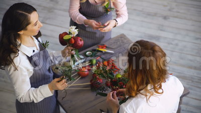 Three young handsome chef florists work at flowers fruit shop making fruit and vegetable bouquet. Top view of three young handsome chef florists work at flowers stock video