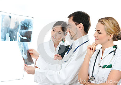Three young medical workers examining x-rays