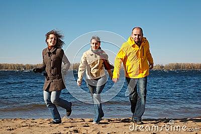 Three young men running down beach at camera