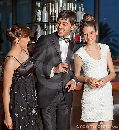 Three young people at bar drinking and flirting