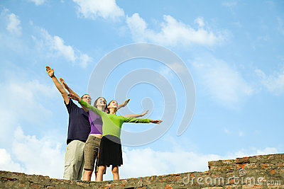 Three young people staying with raised hands