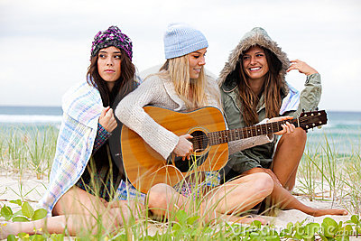 Three Young Women Sitting on Chilly Beach With Gui