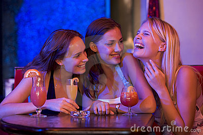 Three young women sitting at a table and laughing