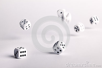 Thrown dice bouncing across a white surface