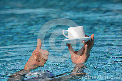 best vacation,hand above water with cup of coffee