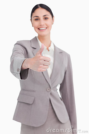 Thumb up given by smiling businesswoman