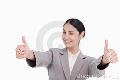Thumbs up given by smiling young businesswoman