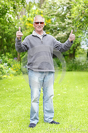 Thumbs up old man in garden