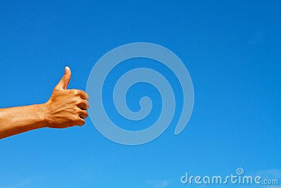 Thumbs up symbol against blue sky