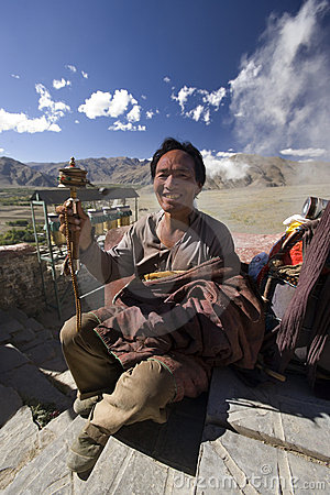 Tibetan Buddhist with prayer wheel in Tibet Editorial Stock Photo